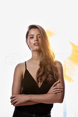 Buy stock photo Studio portrait of an attractive young woman standing with her arms folded against a brightly lit background
