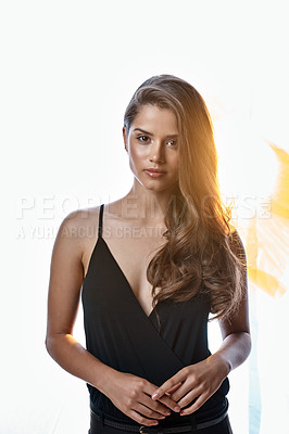 Buy stock photo Studio portrait of an attractive young woman standing against a brightly lit background