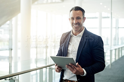 Buy stock photo Cropped portrait of a handsome mature businessman using his tablet while standing in the office