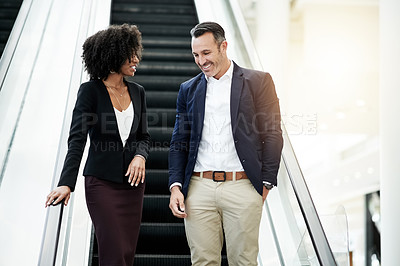 Buy stock photo Cropped shot of two corporate colleagues coming down an escalator in their corporate office