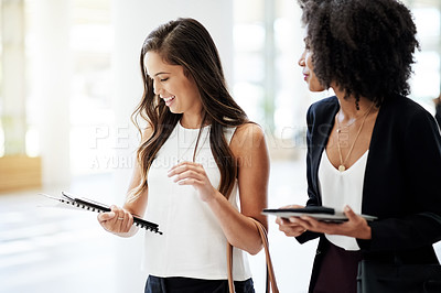 Buy stock photo Cropped shot of two attractive young businesswomen talking while walking through their corporate office