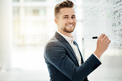 Buy stock photo Cropped portrait of a handsome young businessman strategizing on a whiteboard in his corporate office