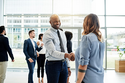 Buy stock photo Cropped shot of two businesspeople shaking hands with their colleagues in the background in a corporate office