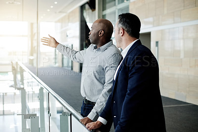 Buy stock photo Cropped shot of a handsome mature businessman showing his male colleague something in their corporate office