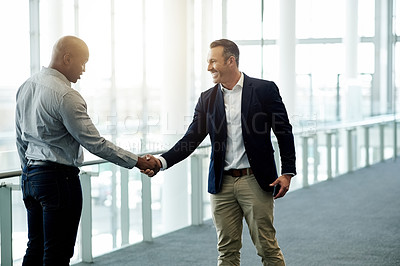 Buy stock photo Cropped shot of two businessmen shaking hands in their corporate office