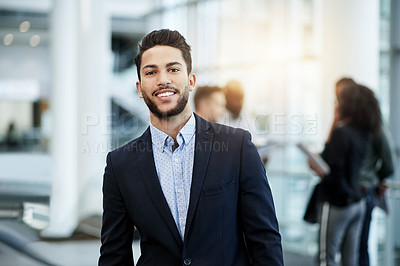 Buy stock photo Portrait of a confident young businessman standing in an office with his colleagues in the background