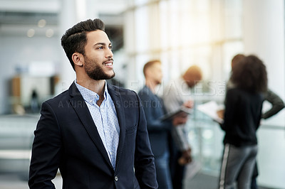 Buy stock photo Shot of a confident young businessman looking thoughtful in an office with his colleagues in the background