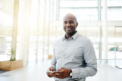 Buy stock photo Portrait of a mature businessman using a cellphone in an office