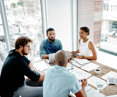 Buy stock photo High angle shot of a group of young businesspeople having a meeting around a table in an office
