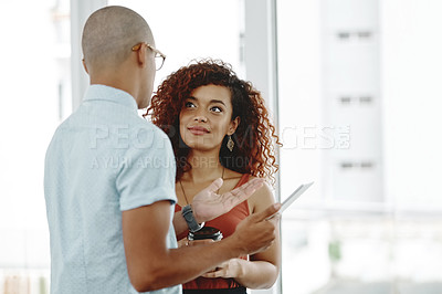 Buy stock photo Shot of two young businesspeople standing and having a discussion in an office