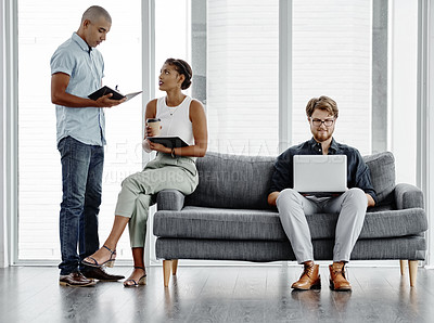 Buy stock photo Full length shot of three young businesspeople gathered around a couch and doing their work in an office