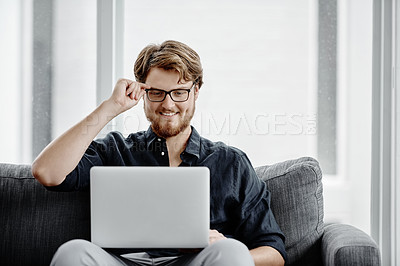 Buy stock photo Shot of a young businessman sitting on a couch and using his laptop in an office