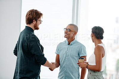 Buy stock photo Shot of two young businessmen shaking hands and coming to an agreement with a collegeau in the background