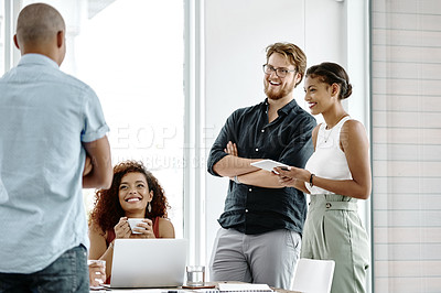 Buy stock photo Shot of a group of cheerful young businesspeople having a discussion in their office