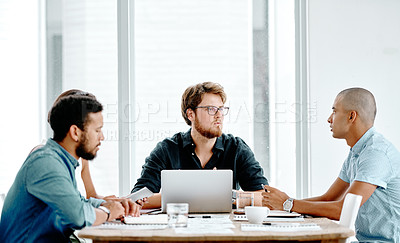 Buy stock photo Shot of three young businessmen having a meeting around a table in an office