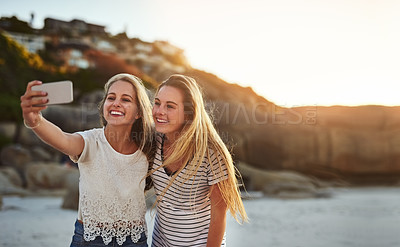 Buy stock photo Shot of two friends taking a selfie while spending the day at the beach