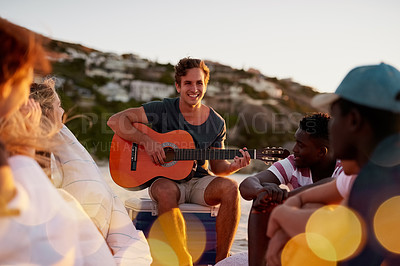 Buy stock photo Shot of a man playing the guitar while sitting on the beach with his friends