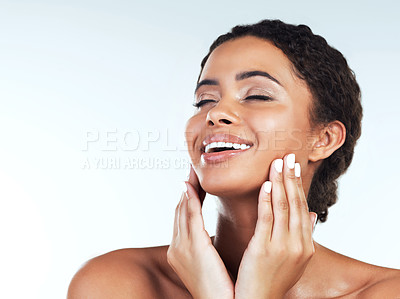 Buy stock photo Studio shot of an attractive young woman posing while touching the sides of her face against a white background