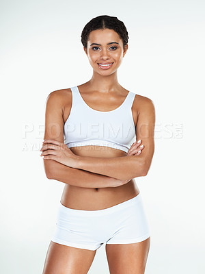 Buy stock photo Portrait of an attractive young woman standing with arms folded against a white background