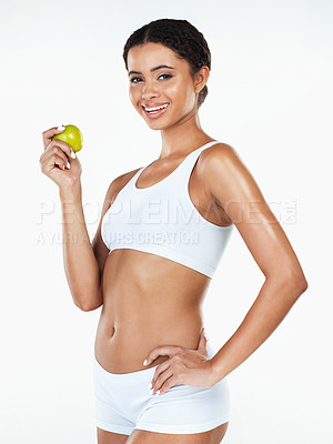 Buy stock photo Portrait of an attractive young woman holding a apple in her hand while standing against a white background