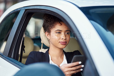 Buy stock photo Cropped shot of an attractive young businesswoman using a smartphone while sitting in her car