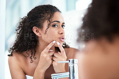 Buy stock photo Cropped shot of a beautiful young woman squeezing a pimple while looking in the mirror