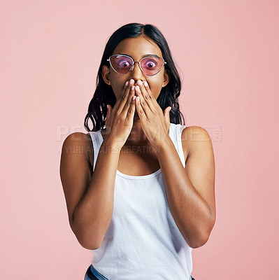 Buy stock photo Studio portrait of a beautiful young woman looking surprised against a pink background