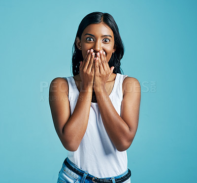Buy stock photo Studio portrait of a beautiful young woman looking surprised against a blue background