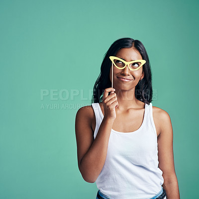 Buy stock photo Studio shot of a beautiful young woman posing with prop glasses against a green background