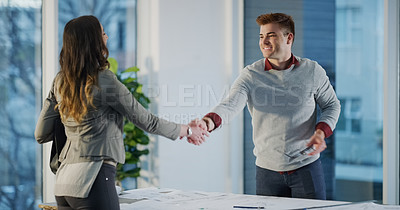 Buy stock photo Cropped shot of two confident businesspeople shaking hands in agreement in the office at work