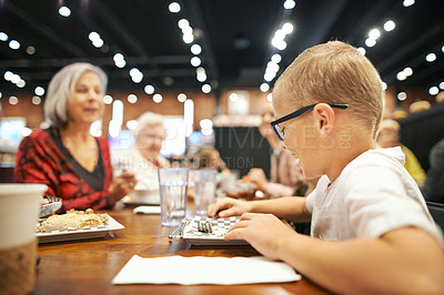 Buy stock photo Shot of a young boy sitting with family in a cafe for lunch