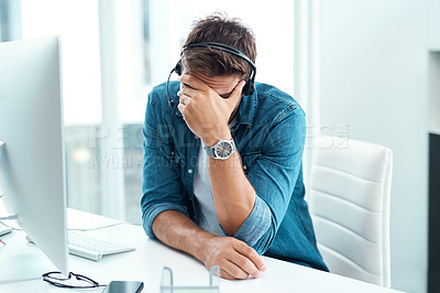 Buy stock photo Shot of a male call centre agent suffering from a headache in his office