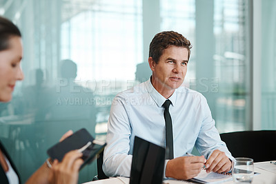 Buy stock photo Shot of a mature businessman sitting in a meeting