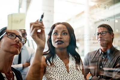 Buy stock photo Shot of businesspeople brainstorming with notes on a glass wall in an office