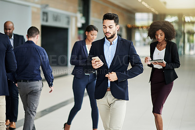 Buy stock photo Shot of a group of corporate business colleagues walking through a convention center