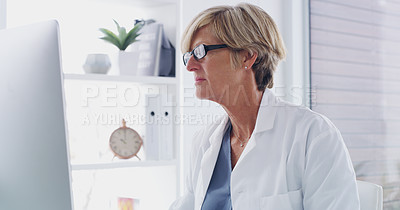 Buy stock photo Shot of a mature doctor working on a computer in her office