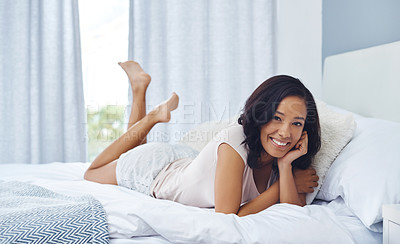 Buy stock photo Shot of a young woman waking up in the morning and using her phone in bed