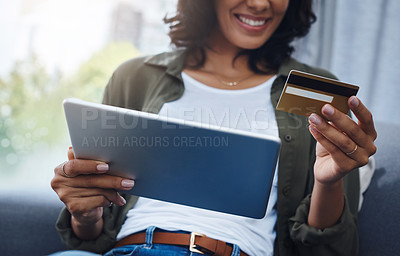 Buy stock photo Shot of a young woman using a digital tablet and credit card on the sofa at home