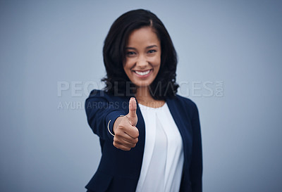 Buy stock photo Studio portrait of a young businesswoman showing thumbs up against a grey background