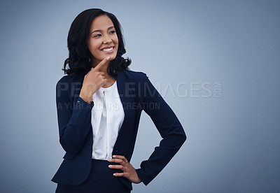 Buy stock photo Studio shot of a young businesswoman looking thoughtful against a grey background