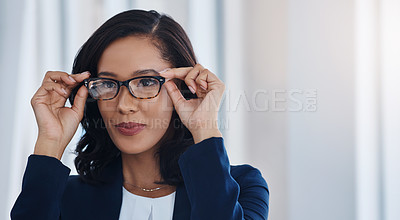 Buy stock photo Shot of a young businesswoman holding a pair of spectacles in an office