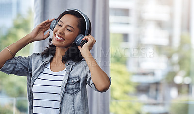 Buy stock photo Shot of a young woman wearing headphones while listening to music at home