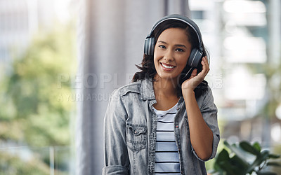 Buy stock photo Portrait of a young woman wearing headphones while listening to music at home