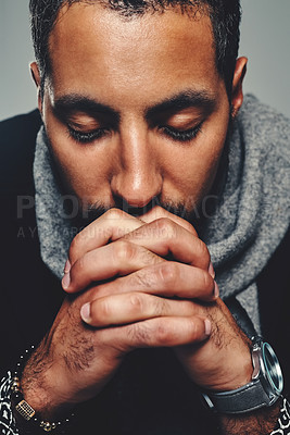 Buy stock photo Studio shot of a handsome young man praying against a grey background