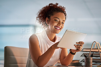 Buy stock photo Shot of a young businesswoman using a digital tablet at her office desk during a late night at work