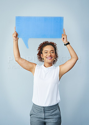 Buy stock photo Studio shot of an attractive corporate businesswoman holding up a speech bubble against a gray background