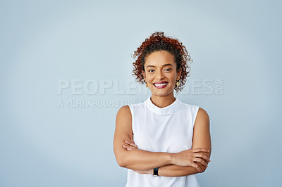 Buy stock photo Studio portrait of a confident young businesswoman posing against a gray background