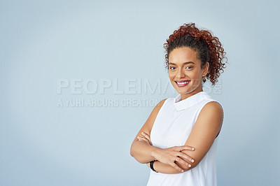 Buy stock photo Studio portrait of a confident young businesswoman posing with her arms folded against a gray background