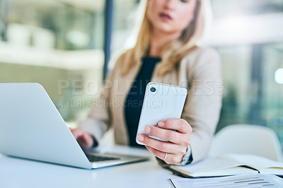 Buy stock photo Cropped shot of an attractive young businesswoman sending texts while working in her corporate office