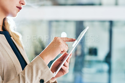 Buy stock photo Cropped shot of an unrecognizable young businesswoman working on a tablet in her corporate office